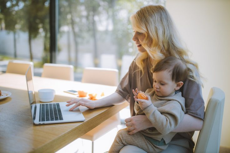 woman carrying her baby and working on a laptop 4079281